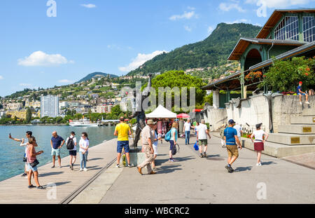 Montreux, Switzerland - July 26 2019: People around the statue of Freddie Mercury, singer of famous band Queen. Tourists taking photos. Promenade by Lake Geneva. Popular tourist attraction. - Stock Photo