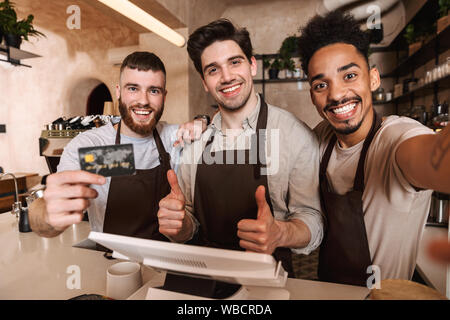 Three cheerful men baristas standing behind the counter at the coffee shop, taking a selfie, showing credit card - Stock Photo