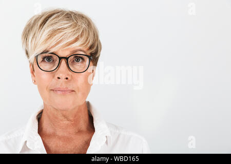 Portrait closeup of caucasian middle-aged woman wearing eyeglasses looking at camera isolated over white background in studio - Stock Photo