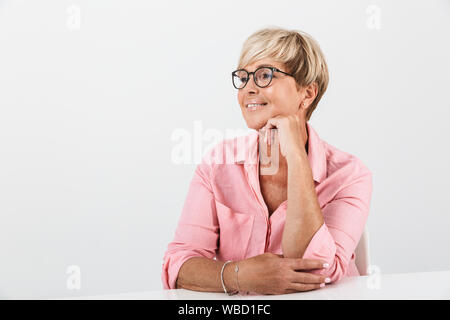 Portrait closeup of positive middle-aged woman with short blond hair smiling while sitting at table isolated over white background - Stock Photo