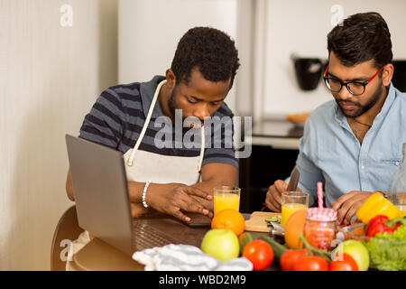 Shot of young indian bearded man in glasses cutting vegetables on wooden chopping board while his african friend wearing apron using mobile phone and - Stock Photo