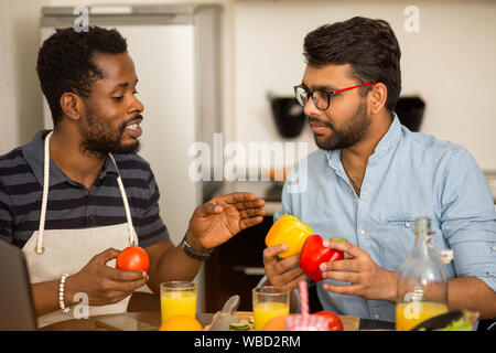 Closeup shot of two multi ethnic bearded friends in casual clothes preparing vegetable salad or smoothie, sitting at table talking using laptop comput - Stock Photo