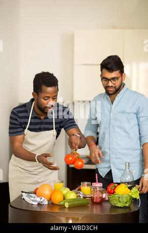 Shot of two male friends preparing vegetable salad in kitchen. Multi ethnic students cooking dinner together in hostel. Dieting, vegetarianism concept - Stock Photo