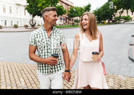 Image of cheerful young couple in summer clothes smiling and holding hands together while walking through city street with paper cups - Stock Photo