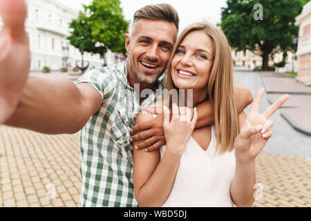 Image of lovely young couple in summer clothes showing peace sign and taking selfie photo together while walking through city street - Stock Photo