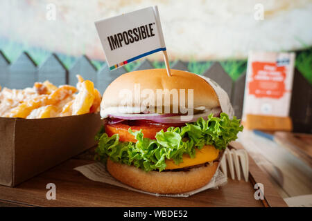 An Impossible™ burger served perfectly at VeganBurg. 100% plant-based patty, lettuce, tomato, cheese, onion, pickle, sauces. - Stock Photo