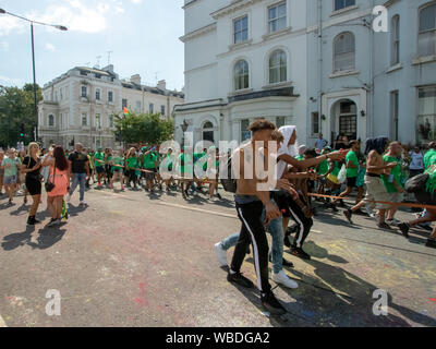 Masqueraders moving along a road behind a sound system truck, during the celebration.The main events of Notting Hill Carnival 2019 got underway, with over a million revellers hitting the streets of West London, amongst floats, masqueraders, steel bands, and sound systems. - Stock Photo