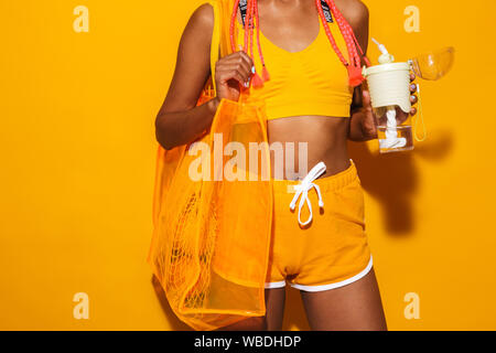 Image cropped of sporty african american woman wearing sunglasses carrying bag and holding plastic cup isolated over yellow background - Stock Photo