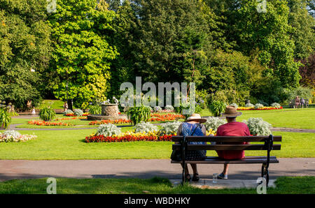 Women resting on park bench on very hot weather, Bank Holiday Monday, Valley Gardens, Harrogate, UK, 26 August 2019 - Stock Photo