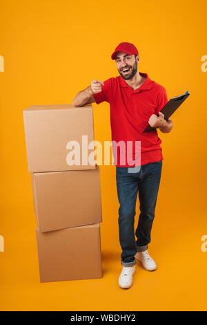 Portrait of young delivery man in red uniform holding clipboard while standing with packaging boxes isolated over yellow background - Stock Photo