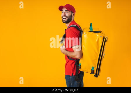 Photo of young delivery man in red uniform carrying backpack with takeaway food isolated over yellow background - Stock Photo