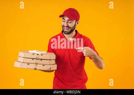 Portrait of young delivery man in red uniform smiling and holding pizza boxes isolated over yellow background - Stock Photo