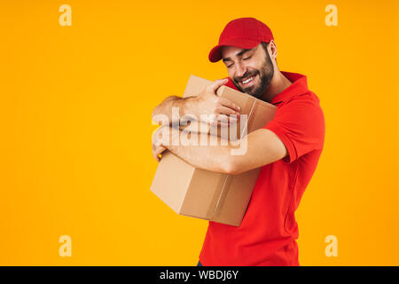 Image of young delivery man in red uniform smiling and hugging packaging box isolated over yellow background - Stock Photo