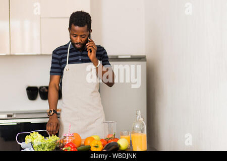 Portrait of serious young unshaven african man wearing apron standing in the white kitchen talking on mobile phone. Closeup shot. Cooking, communicati - Stock Photo