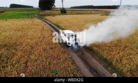 The car broke down, smokes from under the hood, the driver shocked - Stock Photo