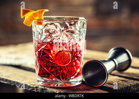 Cocktail Negroni on a old  wooden board. Drink with gin, campari martini rosso and orange - Stock Photo