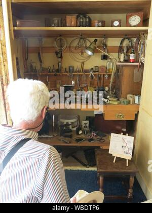 A visitor admires the interior of Lord Nuffield's tool cupboard in his bedroom at Nuffield Place, a time capsule from his engineering days at Cowley. - Stock Photo