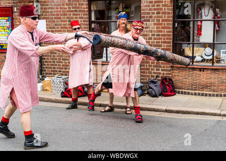 Sandwich folk and Ale Festival. Popular group The Fabulous Fezheads, dressed in Egyptian costume, performs and rolling out a Persian rug in the street - Stock Photo