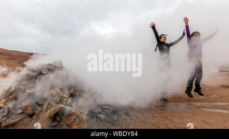 Two women having fun jumping in the steam at the Hverir Geothermal Field by Mt. Namafjall next to Lake Myvatn, Iceland. - Stock Photo