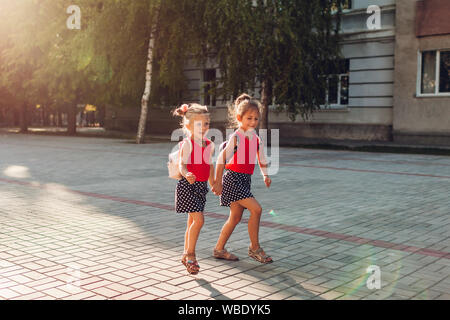 Happy sisters girls wearing backpacks and running. Children pupils having fun near school. Education. Back to school - Stock Photo