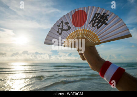 Hand of Japanese sports supporter holding fan decorated with kanji characters spelling out hissho (English translation: certain victory) at the beach - Stock Photo