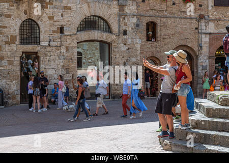 Tourists taking a selfie in Piazza della Cisterna, San Gimignano - Stock Photo