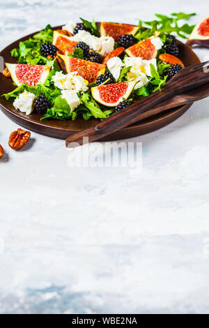 Salad with figs, feta cheese and blackberries in a wooden plate on a white background. - Stock Photo