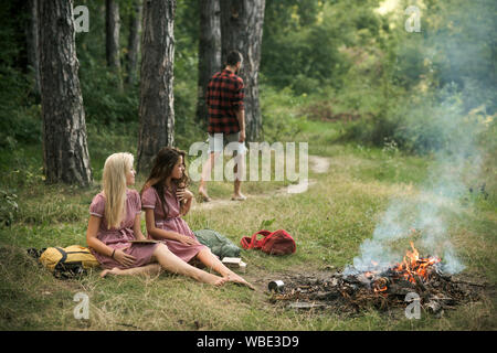 Young girls reading books in forest or park. Beautiful women sitting next to campfire. Guy walking on path into woods