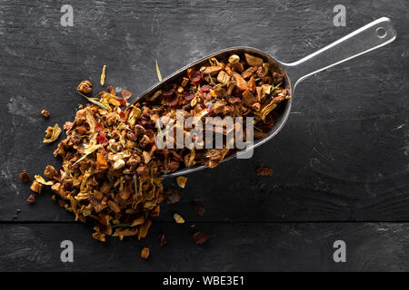 Heap of dried fruit tea infusion with oranges and strawberries mixed with tea leaves and assorted herbs in metal scoop on black wooden table backgroun - Stock Photo