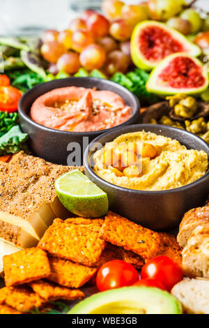 Vegan appetizer platter. Hummus, tofu, vegetables, fruits and bread on a black tray, white background. - Stock Photo