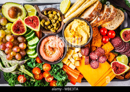 Meat and Cheese appetizer Platter. Sausage, cheese, hummus, vegetables, fruits and bread on a black tray, white background.