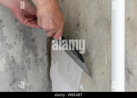 The worker covers the uneven walls, man's hands with a large spatula and putty, apartment repair - Stock Photo