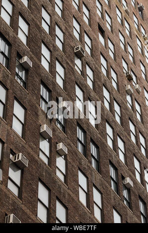 Vertical view of geometric generic windows and air conditioning devices on an industrial brick building at dawn in the United States - Stock Photo