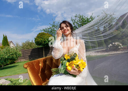 The charming bride keeps a wedding bouquet and sitting on the yard - Stock Photo