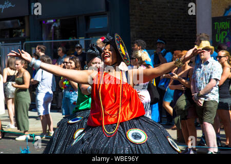 26 August 2019 - Woman in a costume walking in the Notting Hill Carnival parade on a hot Bank Holiday Monday, London, UK - Stock Photo