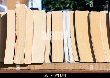 """Stack of books of different size on the shelf. Close-up view  of books at outdoor street market known as """"Sevgi yolu"""" (translated Love Road). - Stock Photo"""