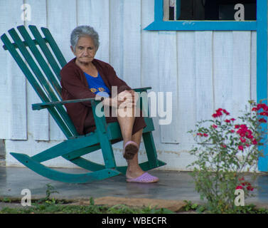 Trinidad, Cuba, Nov 22, 2017 - Old woman sits on green tocking chair on porch against white wall - Stock Photo