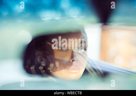 Beautiful woman driver reflecting in the rear view mirror. Driving her car concept. Artistic shot with a few, multiple reflections of the lady face - Stock Photo