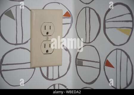 Electrical wall socket on wall paper designed with modern art - Stock Photo