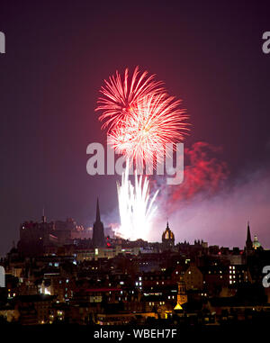 Edinburgh, Scotland, UK. 26 August, 2019. The annual Virgin Money Fireworks Concert, which marks the end of the Edinburgh International Festival, pictured from above Salisbury Crags in the Queens Park against the backdrop of Edinburgh Castle, St Giles Cathedral, The Hub spire, and University Dome in the city centre. - Stock Photo