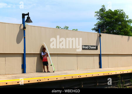 Lone surfer with a surfboard awaits subway train on the Broad Channel platform on a hot summer afternoon on August 18th, 2019 in Queens, New York, USA - Stock Photo