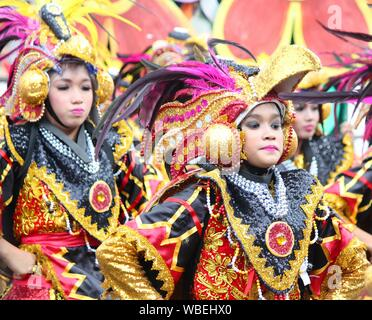 Davao City, Philippines-August 2014: Participants in colorful costumes at the Kadayawan street dancing competition. - Stock Photo
