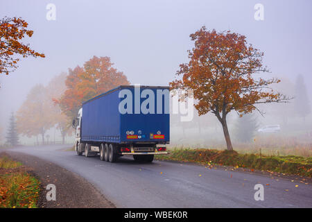 transcarpathia, ukraine - oct 09, 2018: truck on the serpentine in fog. breaking before the road turn. trees in fall foliage. sneaky autumn weather. d - Stock Photo