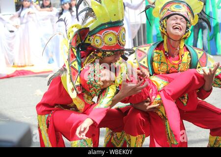 Davao City, Philippines-August 2014: Street parade participants in colorful costumes perform an emotional presentation. Kadayawan is celebrated August - Stock Photo