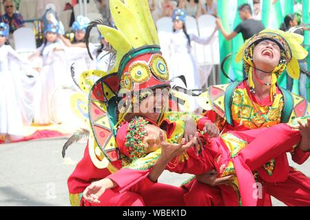 Davao City, Philippines-August 2014: Street dancers in colorful costumes perform an emotional presentation.  Kadayawan is celebrated August each year - Stock Photo