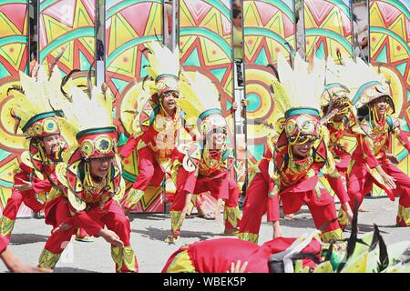 Davao City, Philippines-August 2014: Street dancing participants in colorful costumes and headresses.   Kadayawan is celebrated August each year to gi - Stock Photo