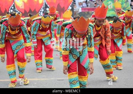 Davao City, Philippines-August 2014: Street dancers in colorful costumes performing for the judges and crowds. Kadayawan is celebrated August each yea - Stock Photo