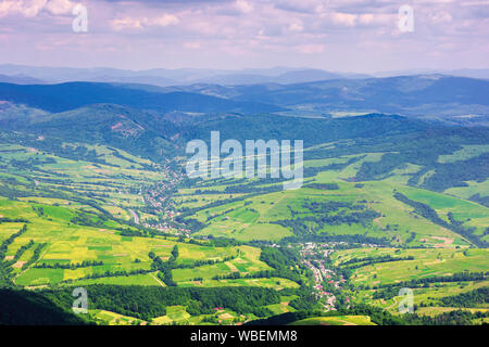 view from a mountain top in to the green valley. beautiful summer landscape of bilasovytsya village, volovets district, transcarpathia region, ukraine - Stock Photo