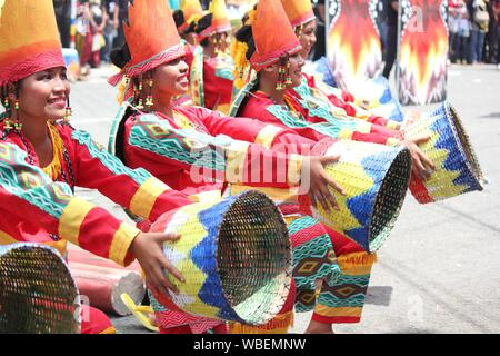 Davao City, Philippines-August 2014: Street dancers in colorful costumes and props during a presentation at the parade. Kadayawan is celebrated August - Stock Photo