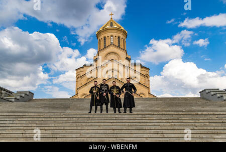 Tbilisi, Georgia - June 8, 2017 - Groomsmen stand in front of the Holy Trinity Cathedral of Tbilisi - Stock Photo